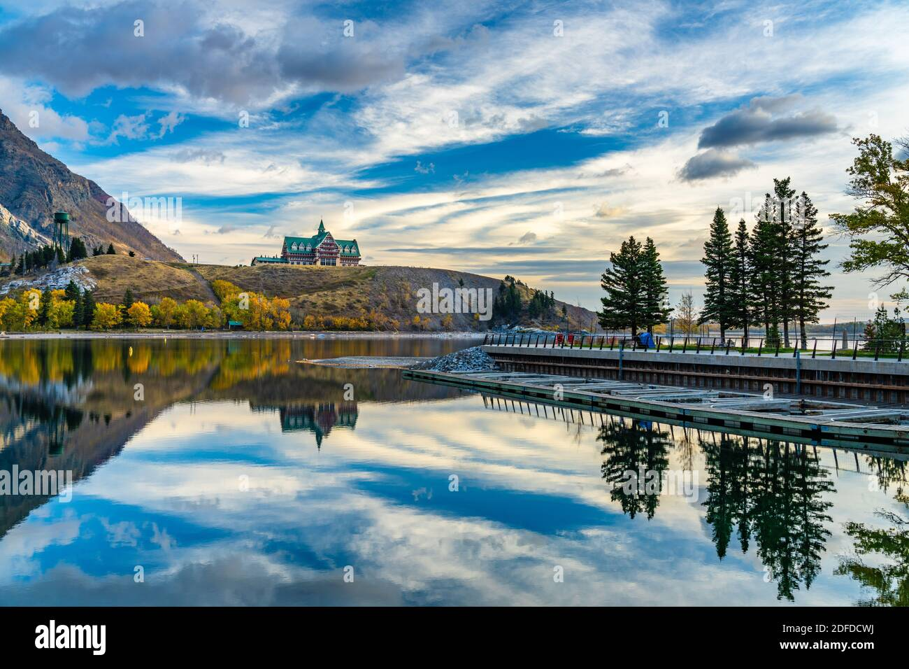 Waterton Lakes National Park lakeshore in autumn foliage season morning. Blue sky, colourful clouds reflect on lake surface like a mirror in sunrise. Stock Photo