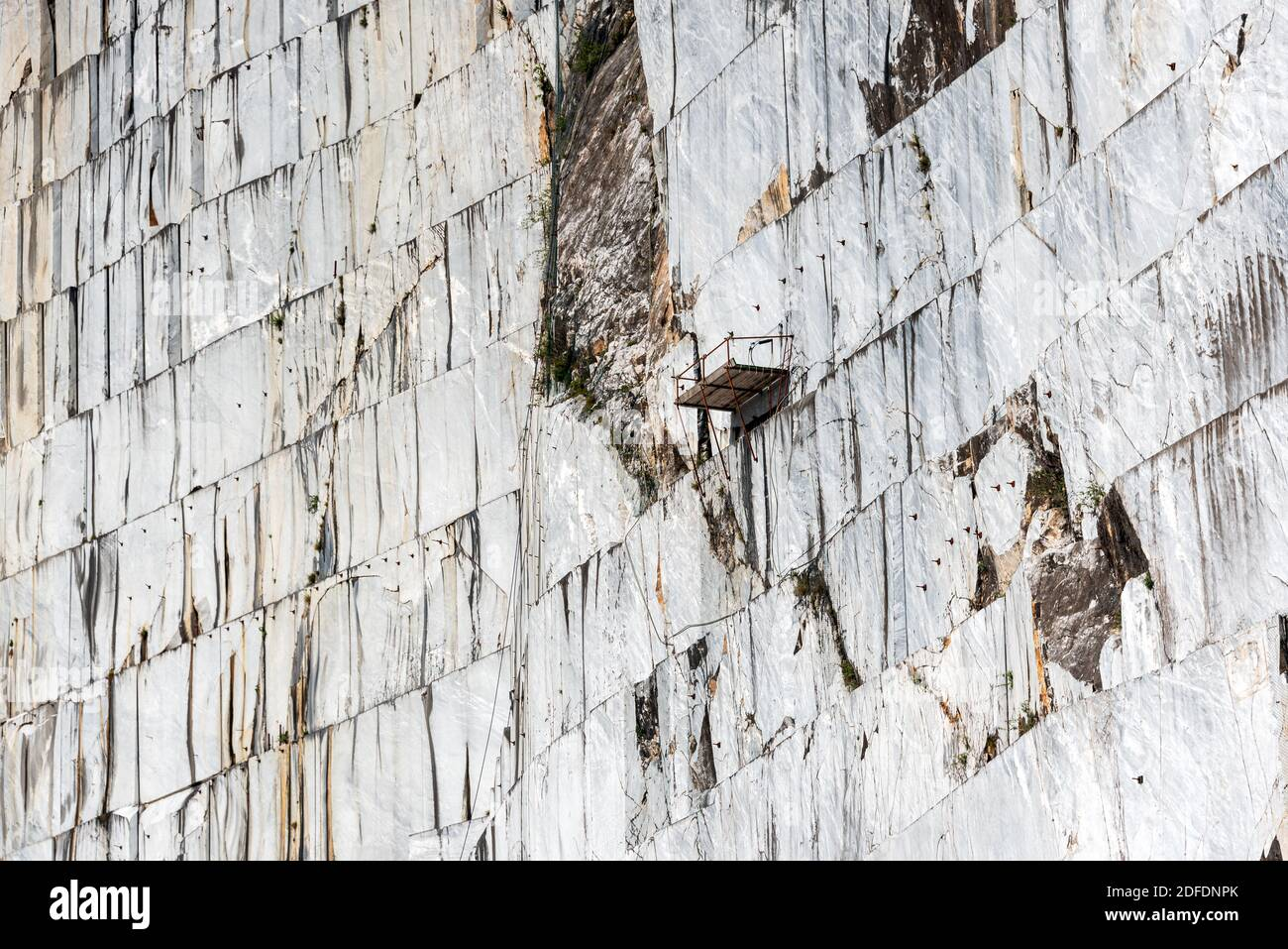 Marble quarry in Carrara, Italy, where Michelangelo got the material for his sculptures. This is the stone wall from which large marble slabs are cut Stock Photo