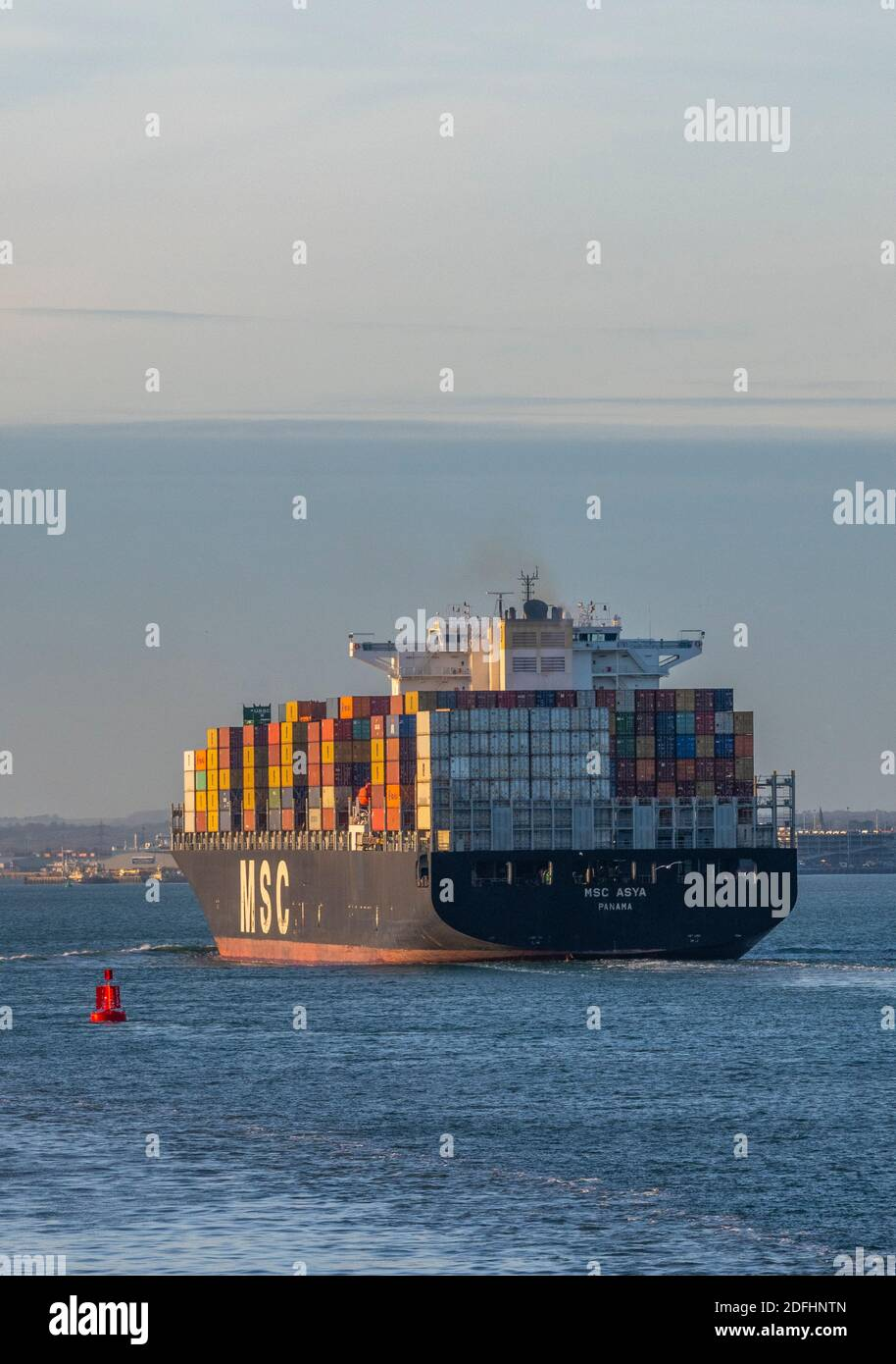 a large container ship MSC asya entering the port of southampton docks with a full cargo or load of colourful containers on board. Stock Photo