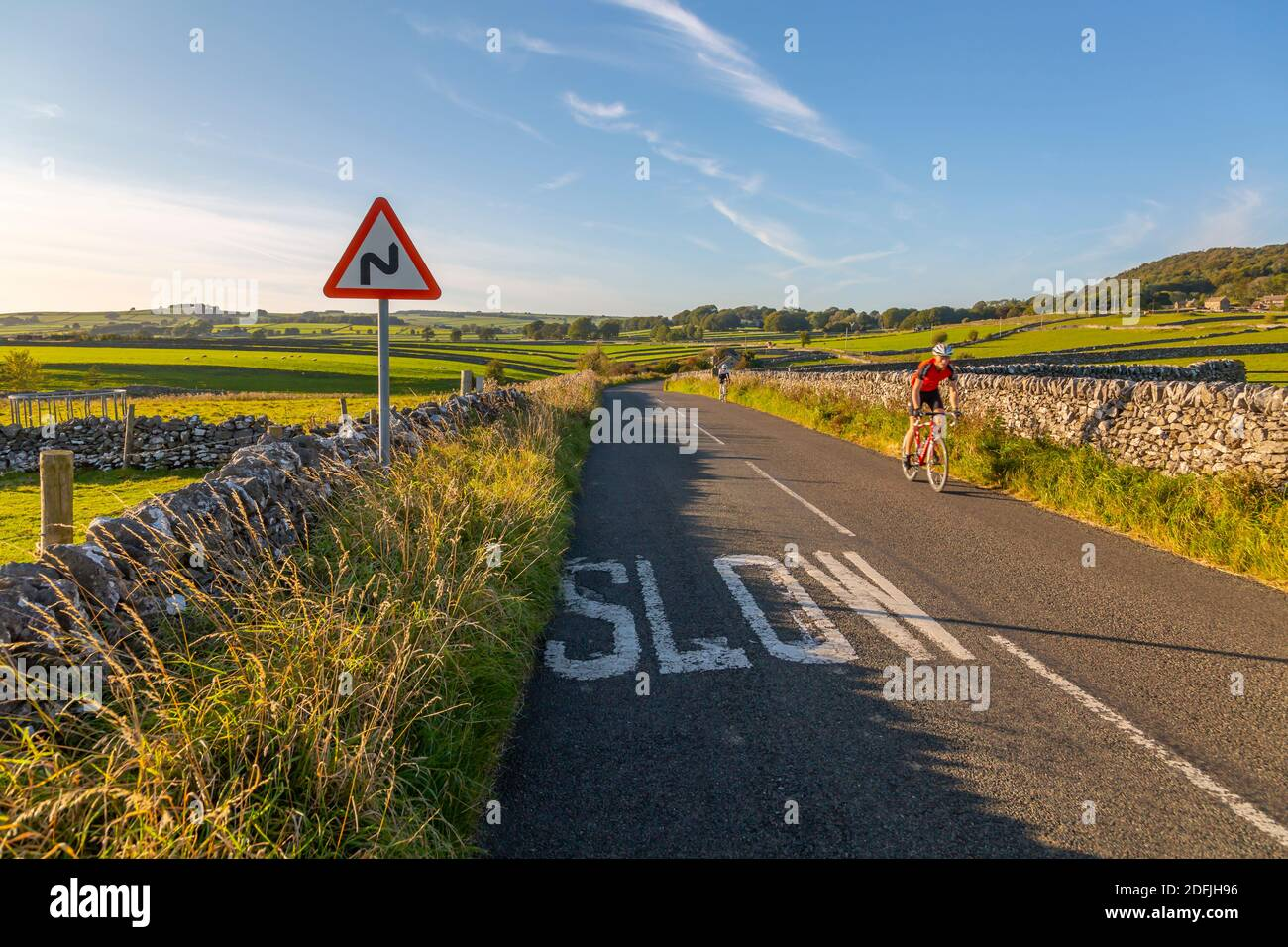View of dry stone walls and cyclist on country lane, Foolow, Derbyshire Peak District, England, United Kingdom, Europe Stock Photo