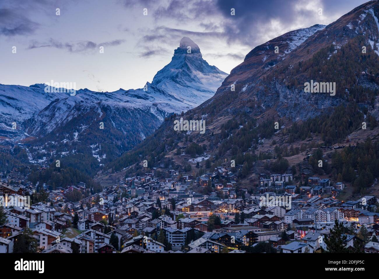 The Swiss village of Zermatt in Valais in autumn at dusk, with the Matterhorn and the Alpine mountain range in the background. Stock Photo