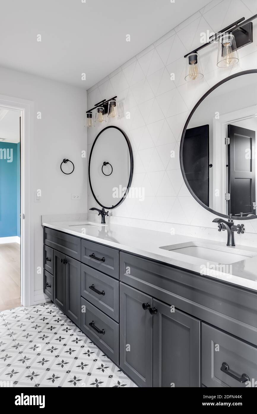 A Beautiful Bathroom With A Dark Grey Vanity Circular Mirrors Black Light Fixtures And A Pattern Tile Floor Looking Towards A Blue Bedroom Stock Photo Alamy