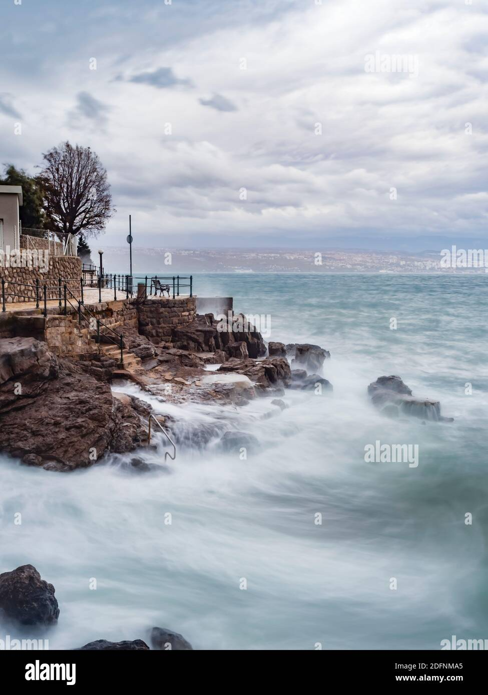 Arty aka artistic view milky smooth surface long exposure severe stormy storm sea waves Lovran rocky rocks coastline Croatia Stock Photo