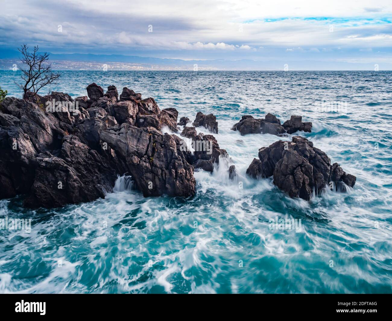 Arty aka artistic view longish exposure severe stormy storm sea waves Lovran rocky rocks coastline Croatia Stock Photo