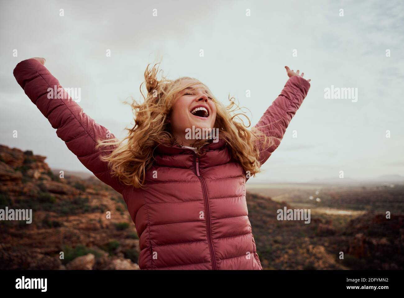 Cheerful young woman with hands raised and outstretched mountaineer with hair flying in wind enjoying fresh breeze - happiness and travel - achieving Stock Photo