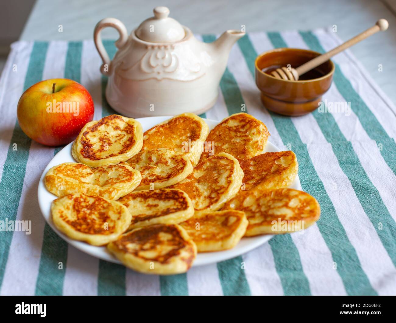 Tasty homemade pancakes laid out on plate near an apple, teapot and bowl of honey . Selective focus on pancakes Stock Photo