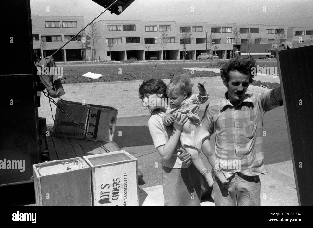 Moving house, family move into new home on a new estate1970s .Father and oldest daughter who is carrying her baby sister. Packing cases, old tea chests coming off the removal van. 1977  Milton Keynes Buckinghamshire UK HOMER SYKES Stock Photo