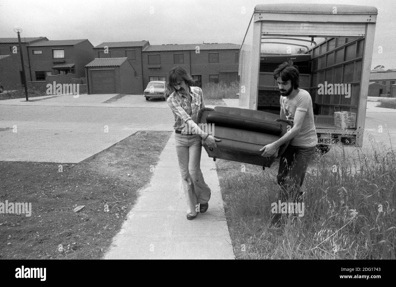 Moving house, removal men carrying furniture into a new family home. 1977. 1970s UK HOMER SYKES Stock Photo