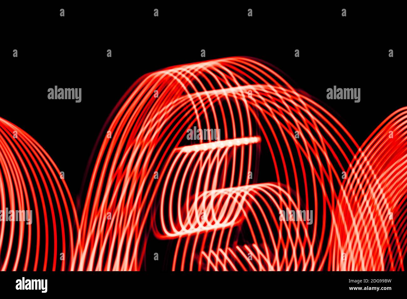 Bright red spiral patterns from light strips on a black background Stock Photo
