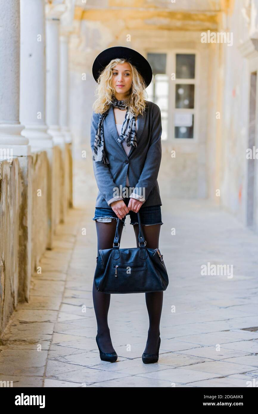 Teengirl blonde curly curls hair is sad indifferent loking away waiting wait in corridor old house Stock Photo