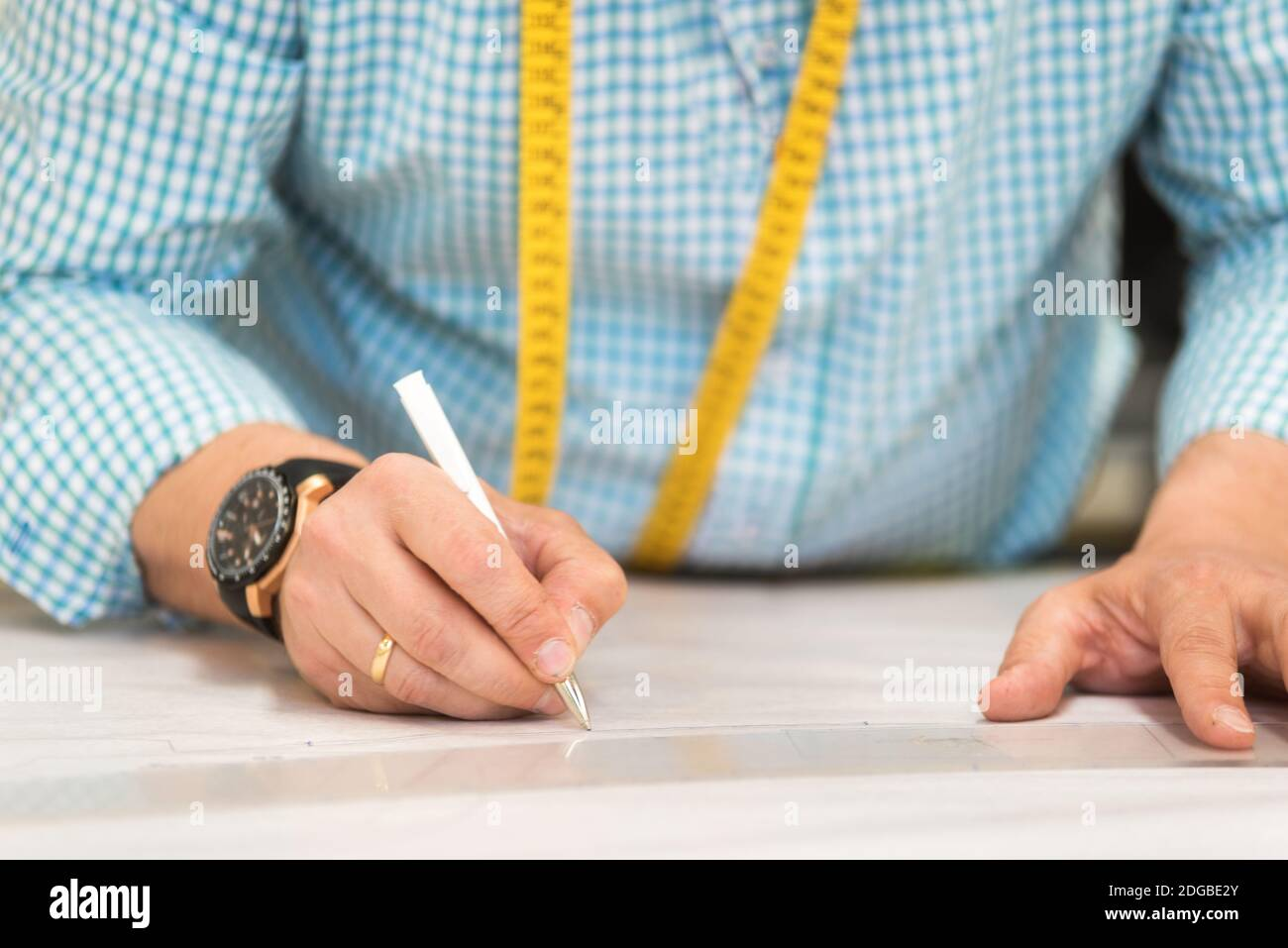 Tailor hands mark drawing on craft paper for making patterns. Stock Photo