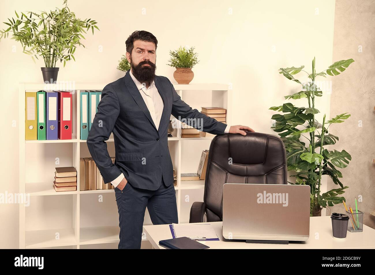 Vacant position. Human resource manager in office. Interviewer welcome job candidate. Man having job interview in company HR department. Empty chair. Bearded boss stand in office. Start career here. Stock Photo