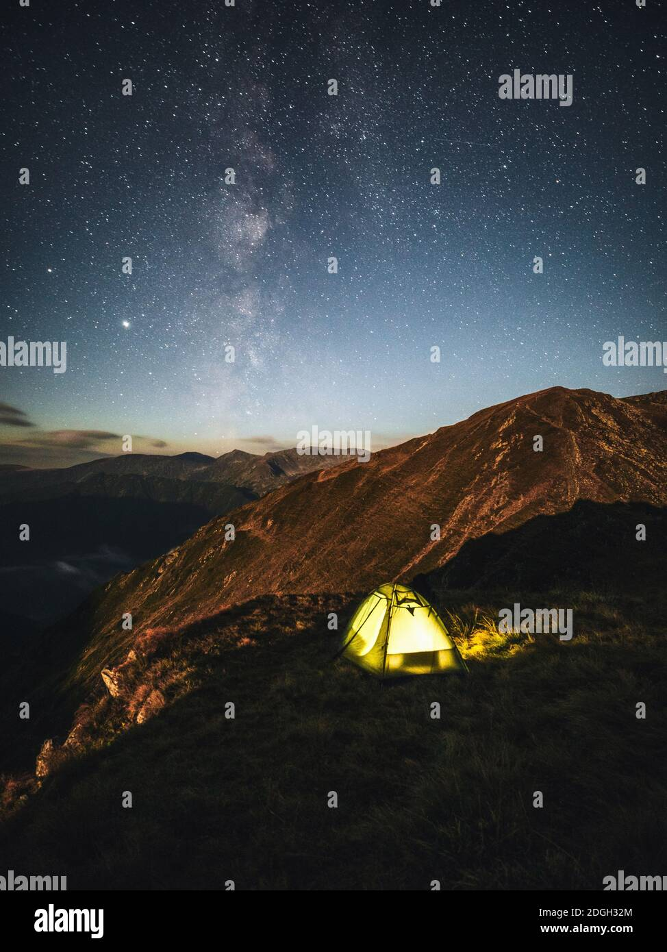 Camping under starry sky and milky way at high altitude on the Carpathian mountains. Illuminated tent in the foreground and majestic mountain peak Stock Photo