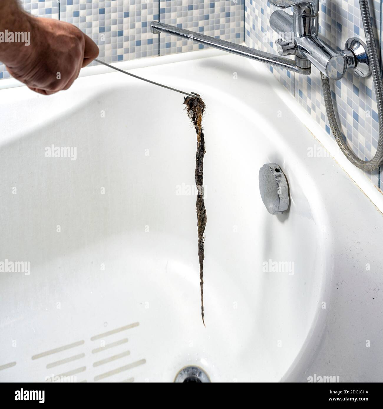 Clogged Drain In The Bathroom A Plumber Pulls Out A Clot Of Dirt With A Tool Stock Photo Alamy