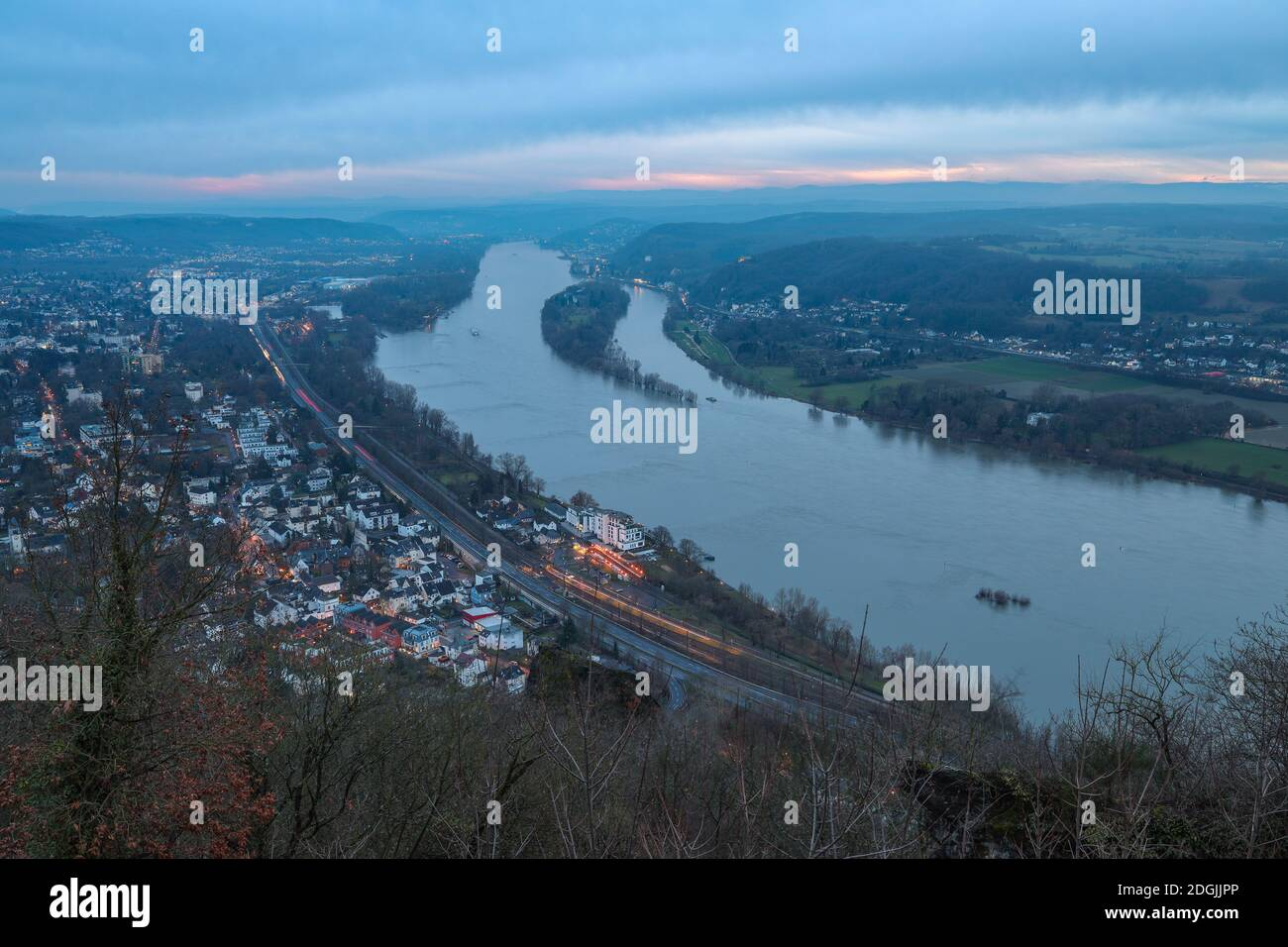 View of Königswinter in Germany along the Rhine River at sunset with cloudy sky. Stock Photo
