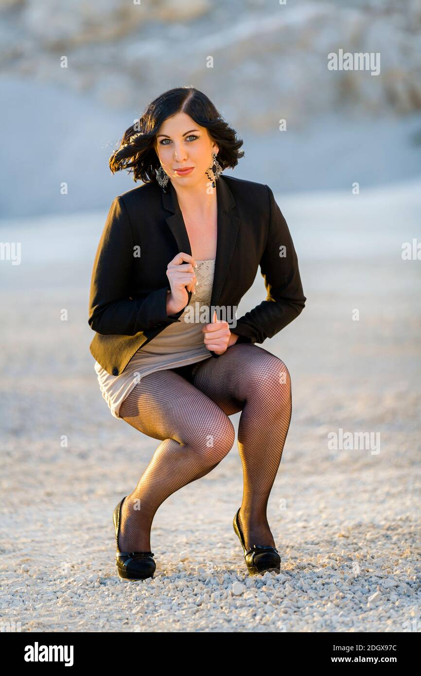 Young 20s woman legs heels squatting squatter squat going to stand get getting up down awkward posture Stock Photo