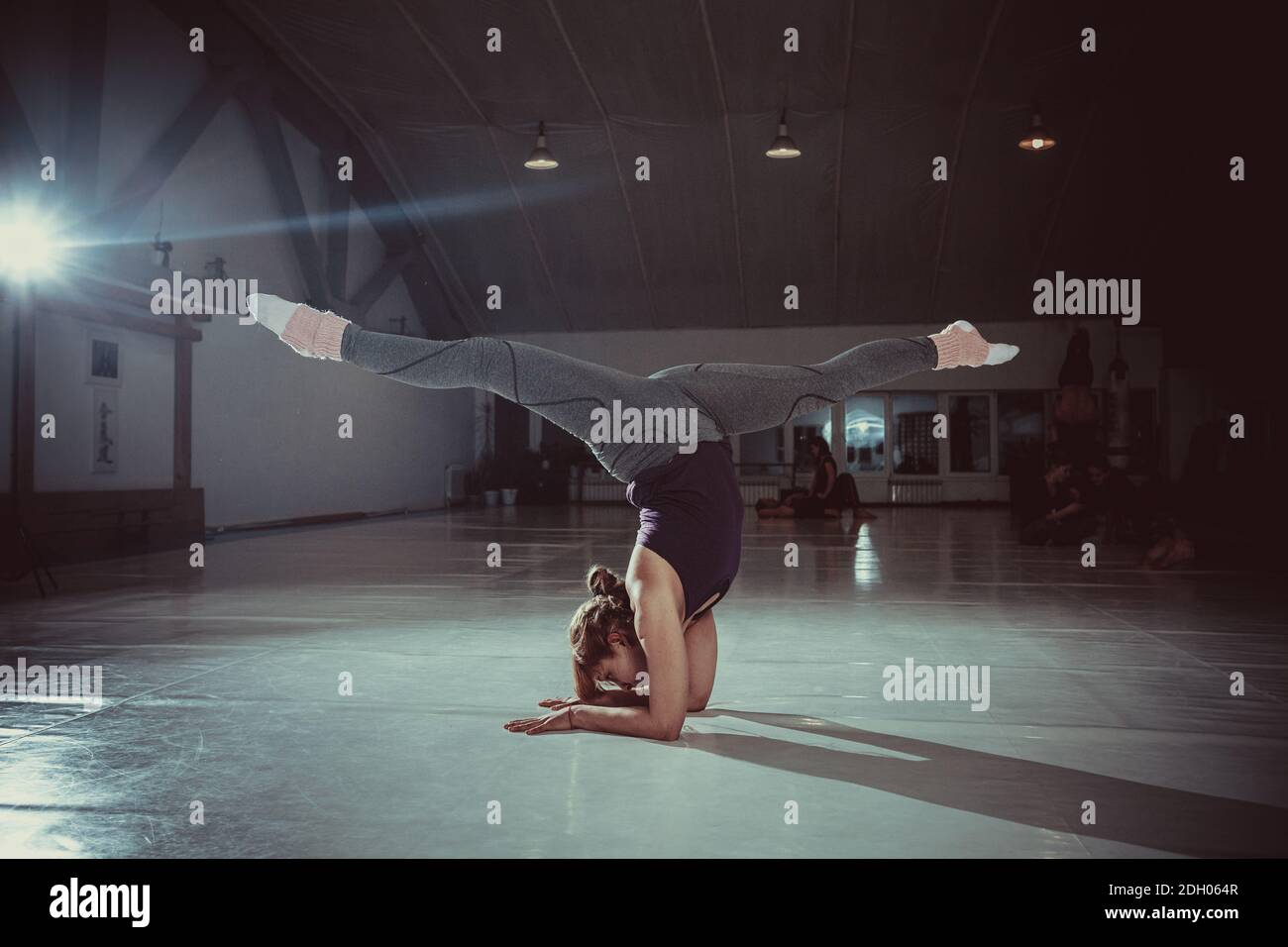 Young attractive yogi woman practicing yoga concept, standing in variation of Pincha Mayurasana exercise, handstand pose, workin Stock Photo
