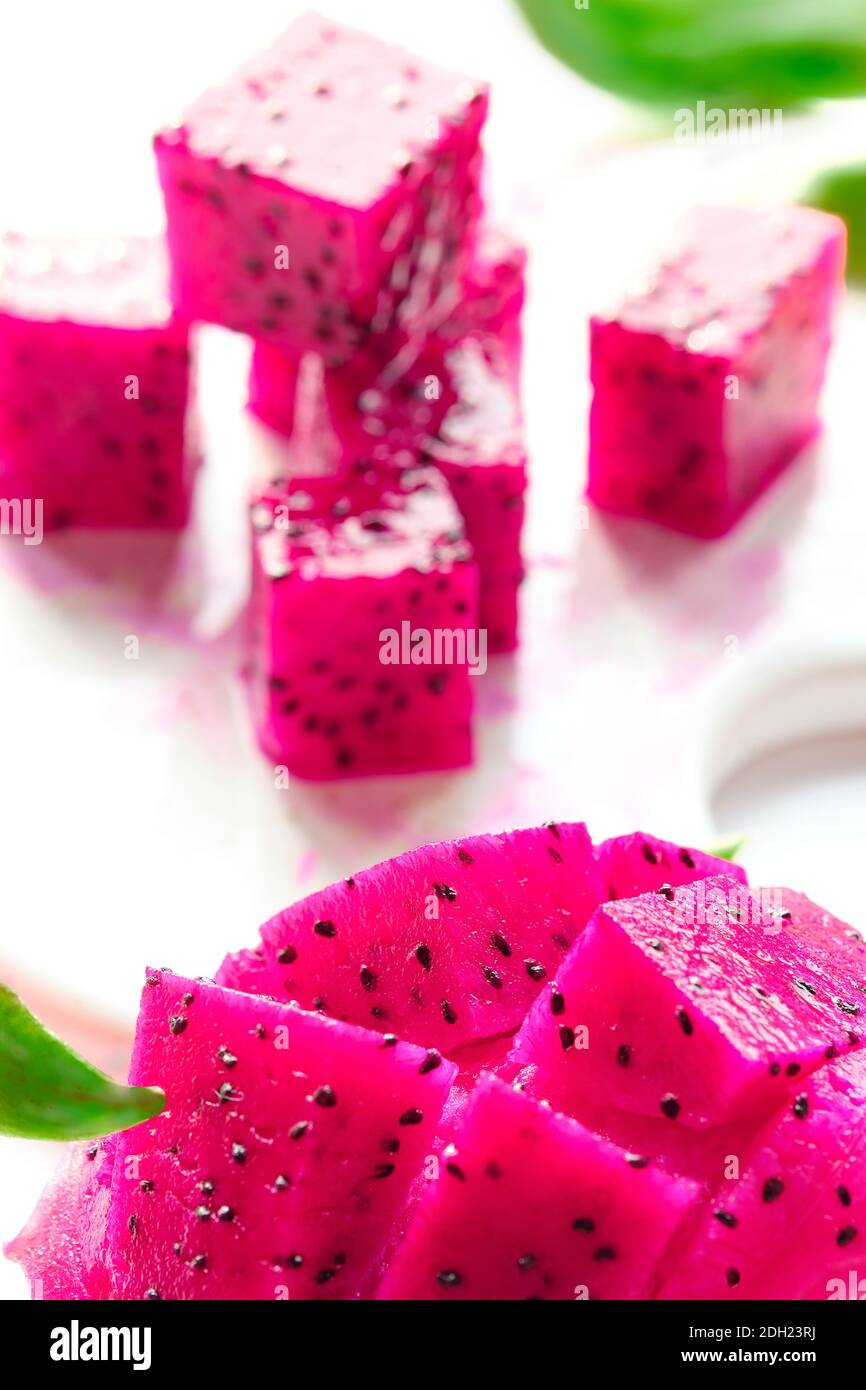 Pink dragon fruit, pitaya or pitahaya cut in cubes on cutting board. Trendy superfood. Stock Photo