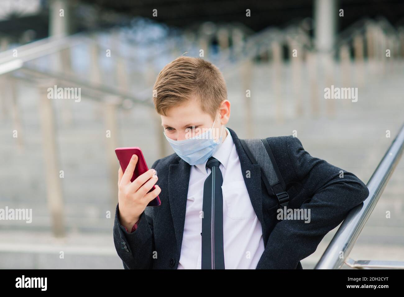 Schoolboy walks out of school wearing protective mask in the city Stock Photo