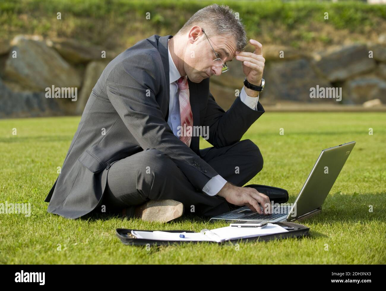 Geschäftsmann sitzt auf einer Wiese, Laptop, Computer, MR:Yes Stock Photo