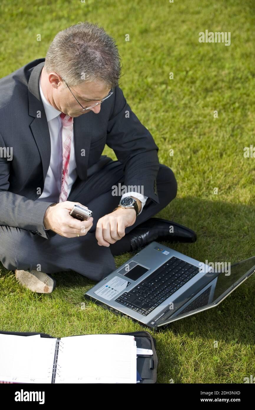 Geschäftsmann sitzt auf einer Wiese, schaut auf die Uhr, Laptop, Computer, MR:Yes Stock Photo