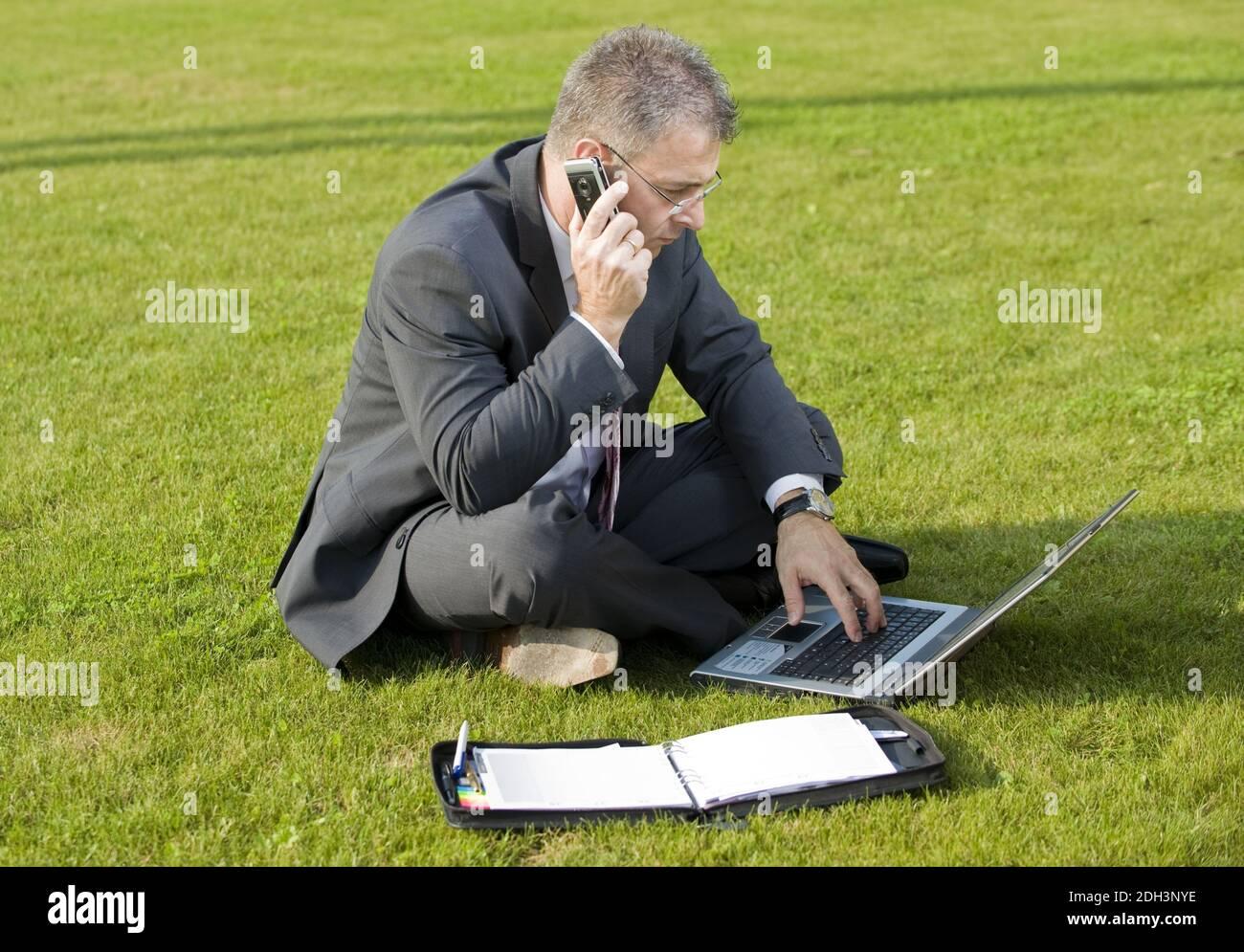Geschäftsmann sitzt auf einer Wiese, telefoniert, Laptop, Computer, MR:Yes Stock Photo