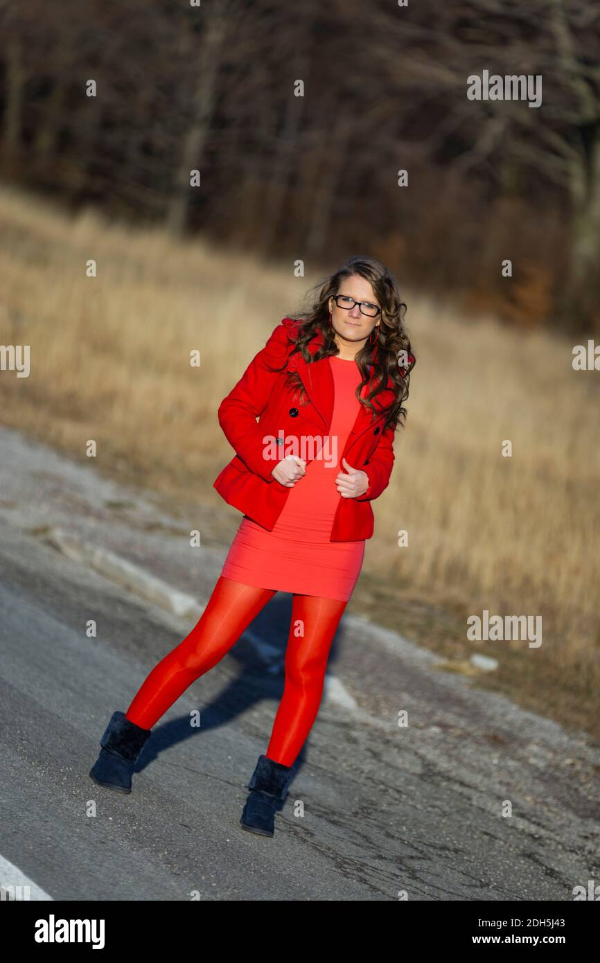 Teengirl posing strike striking pose on road curly curls long hair full length whole body eyeshot eyes eye contact looking at camera Stock Photo