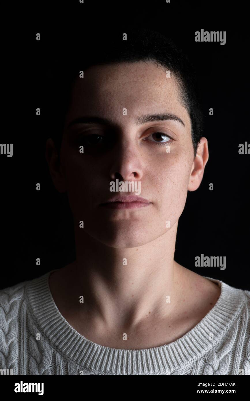 Shadowy portrait of beautiful woman looking at camera Stock Photo