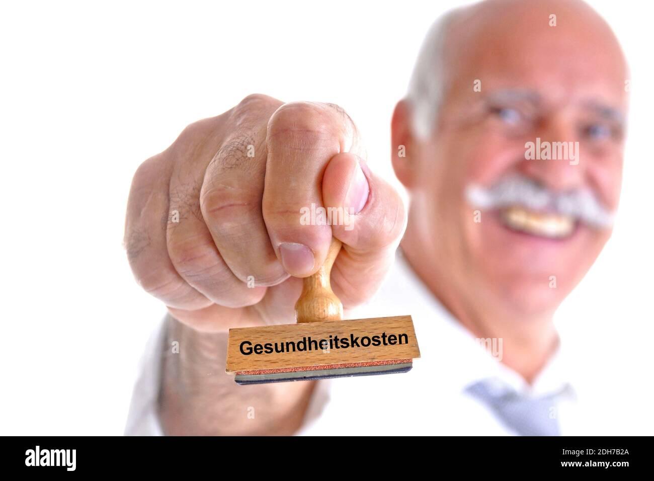 Arzt, Apotheker, Doktor, 65, 70, Jahre, Mann hält Stempel in der Hand, Aufschrift: Gesundheitskosten, Stock Photo