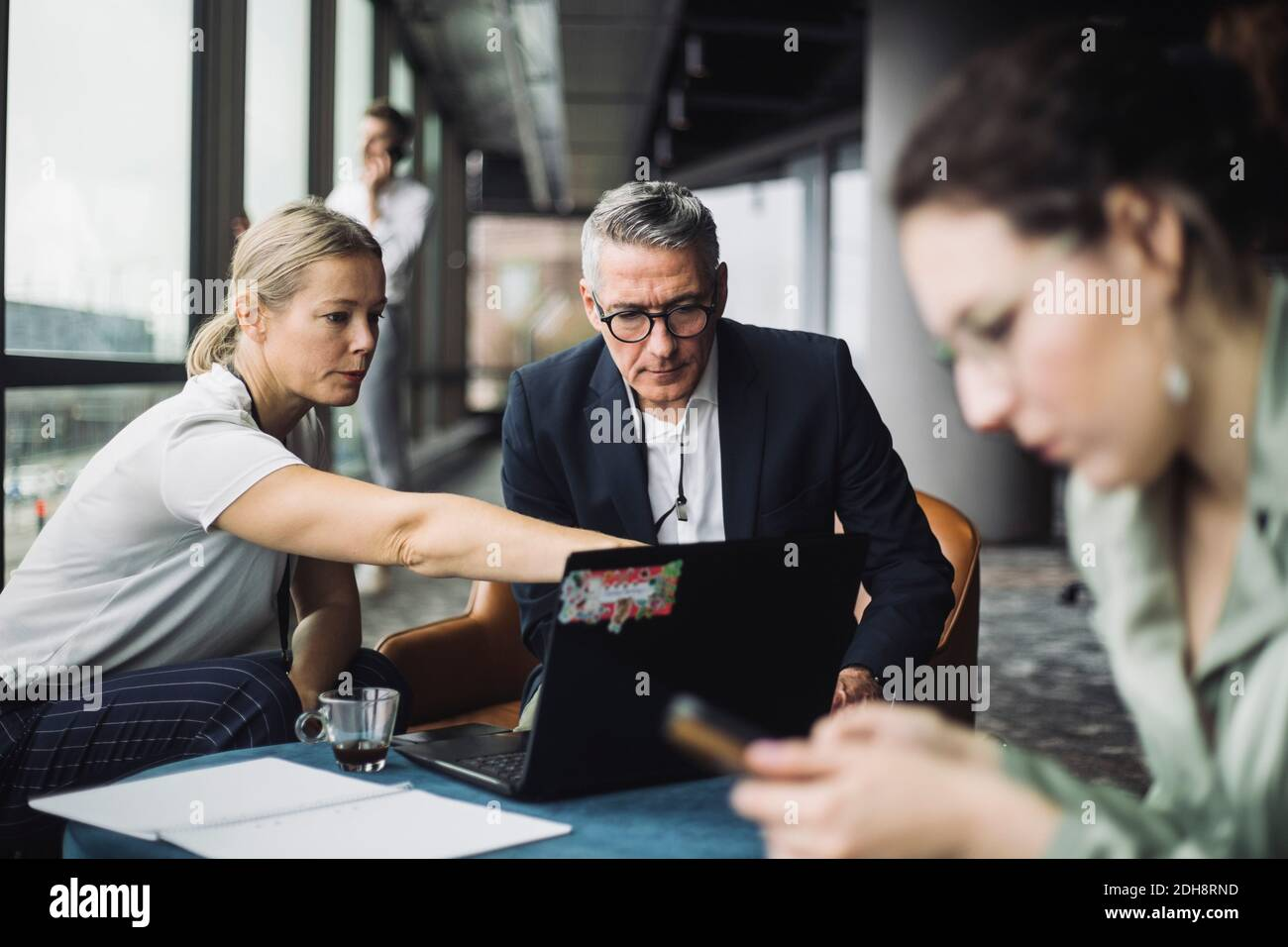 IT professional assisting contemplating businessman in office corridor Stock Photo