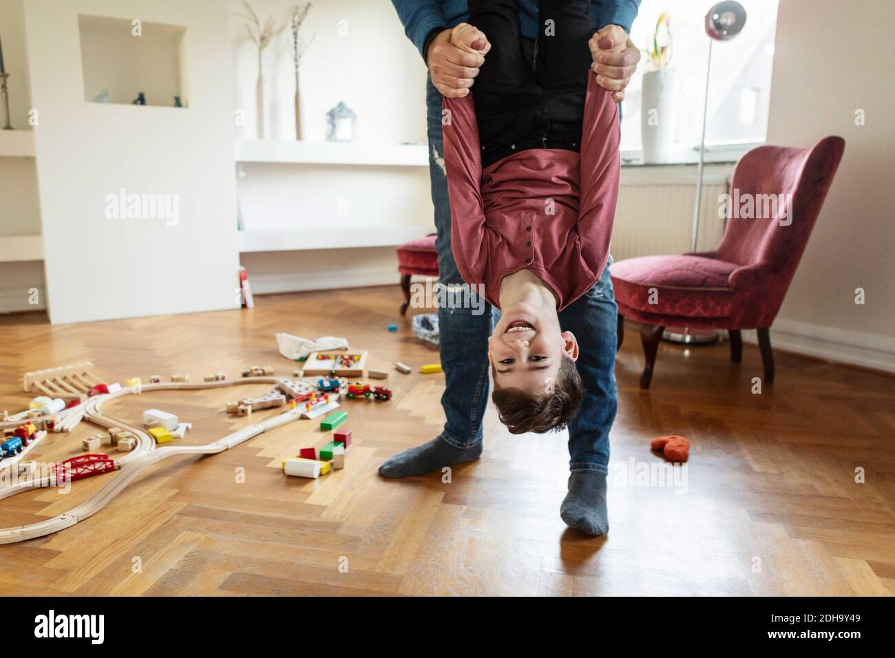Low section of father lifting son in living room Stock Photo