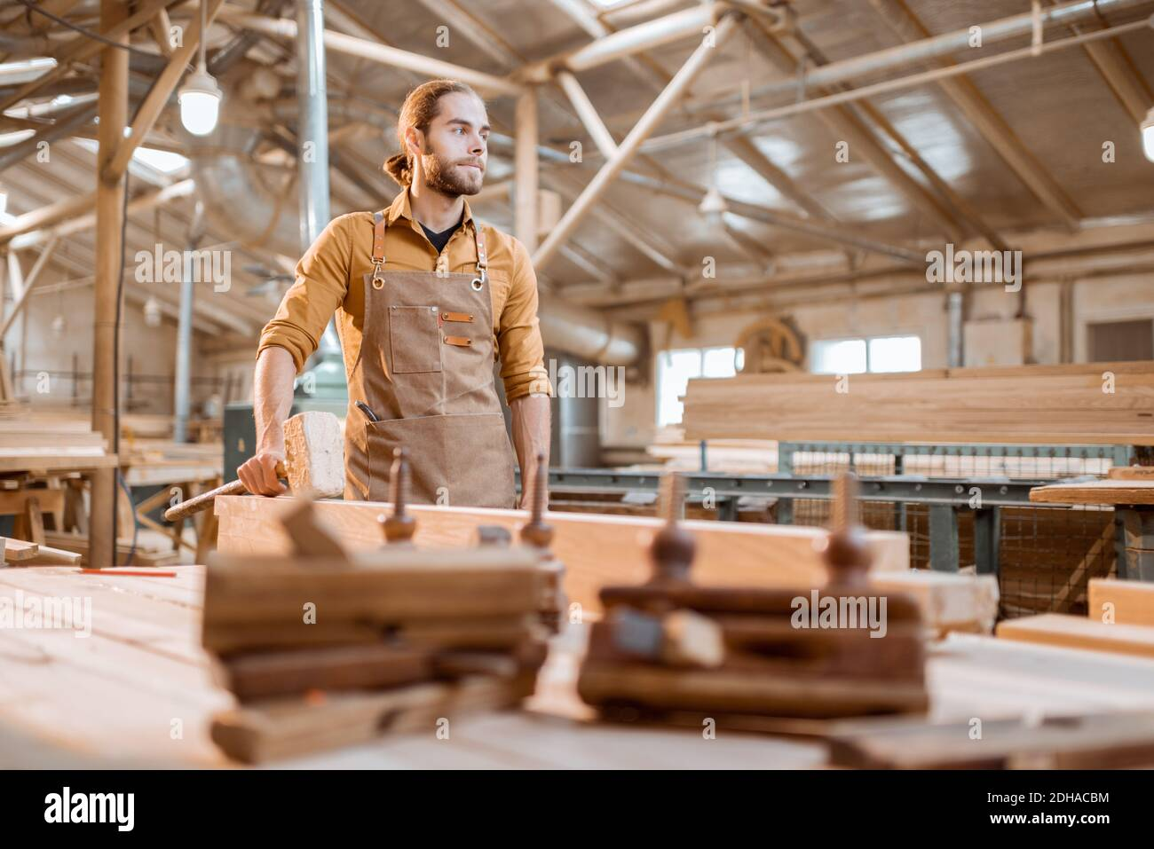 Portrait of a handsome carpenter, standing near the workbench at the old craft joinery Stock Photo