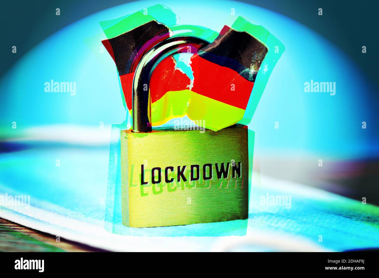 FOTOMONTAGE, Geschlossenes Vorhängeschloss mit angerissener Deutschlandfahne und Aufschrift Lockdown, Spaltung der Gesellschaft durch den Lockdown Stock Photo