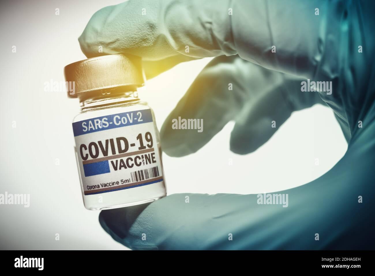 Hand im Latexhandschuh hält Injektionsfläschchen mit Corona-Impfstoff, Symbolfoto Corona-Impfmittel Stock Photo