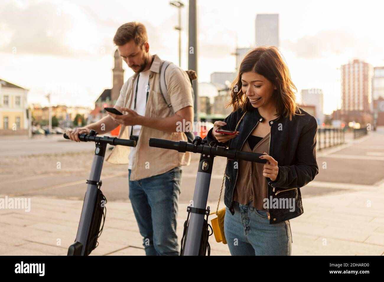 Male and female commuters scanning through mobile phone while unlocking electric push scooters in city Stock Photo
