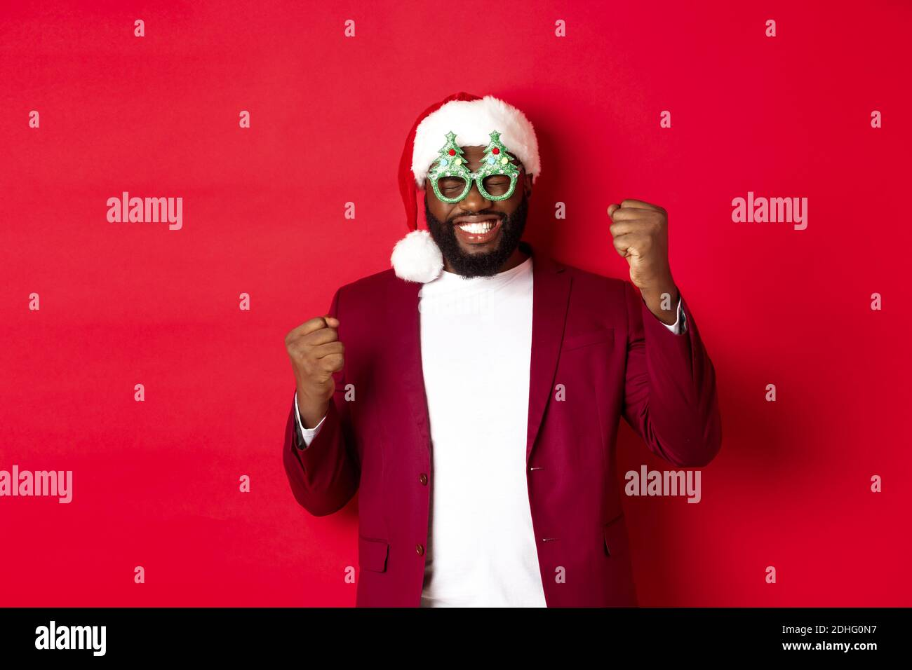 Merry Christmas. Cheerful Black man wearing funny party glasses and santa hat, smiling joyful, celebrating winter holidays, stan Stock Photo