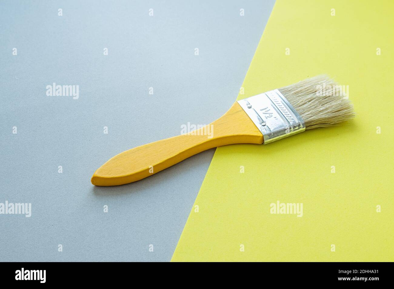 Yellow paint brush on yellow and gray background. Trending color of the year. Home remodeling and renovation concept. Stock Photo
