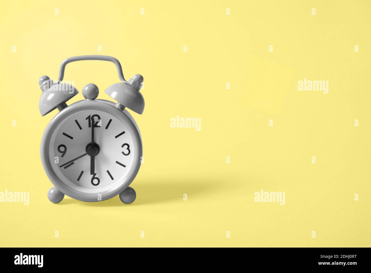 Gray analogue alarm clock showing six in the morning on background of the illuminating yellow tone. Copy space. The main color trend of the year 2021. Stock Photo