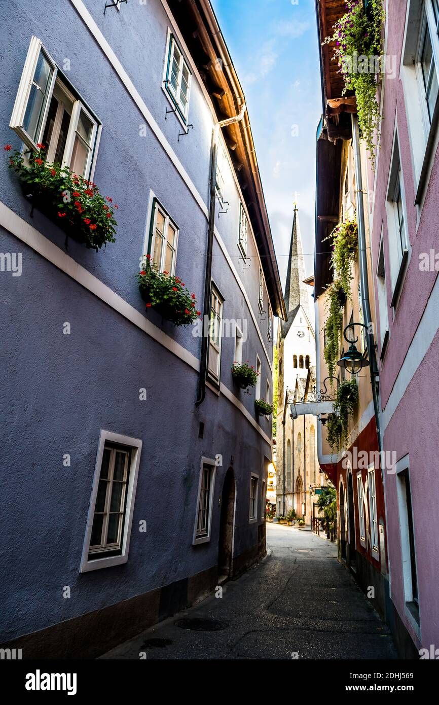 Narrow Alley With Historic Buildings And View to Church In Picturesque Lakeside Town Hallstatt In Austria Stock Photo