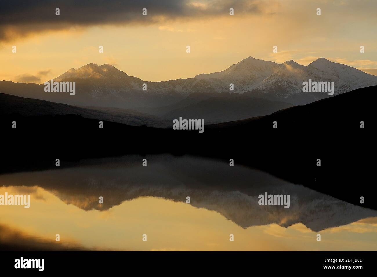 Sunset over the Snowdon horseshoe across showing recent snowfall beyond a flat calm Llynnau Mymbyr. Wales.  Picture taken 5th December 2020 Stock Photo