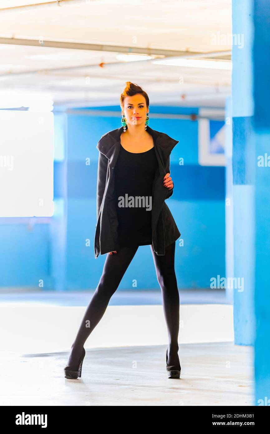 Teengirl in empty parking lot with Blue walls eyeshot eyes eye contact looking at camera legs heels standing front facing frontal view spreading open Stock Photo