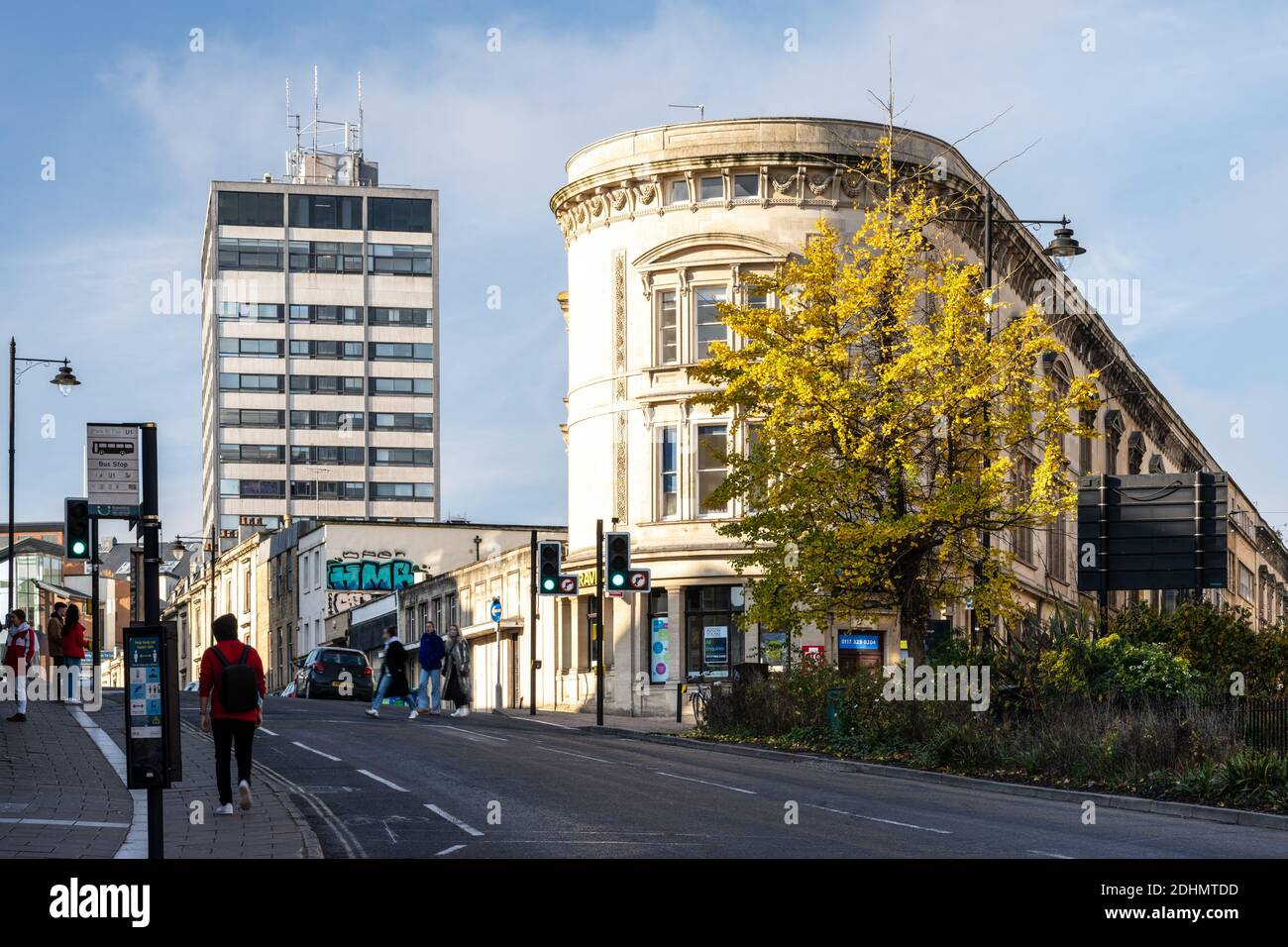 A tree displays autumn colours outside traditional mixed-use apartment and shop buildings on the Queen's Road Triangle in Bristol, with the Clifton He Stock Photo