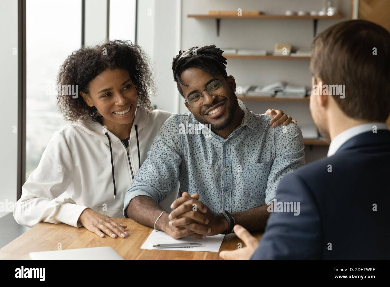 Happy biracial couple have meeting male broker Stock Photo