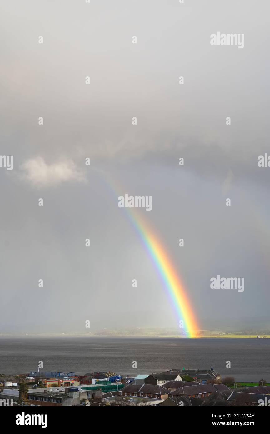 Bright rainbow high in sky over the sea during dark storm Stock Photo