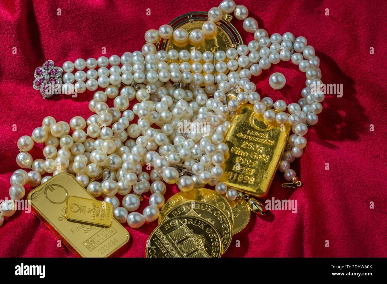 Gold in Münzen und Barren mit Schmuck auf rotem Samt. Symbolfoto für Reichtum, Luxus, Reichensteuer. Stock Photo