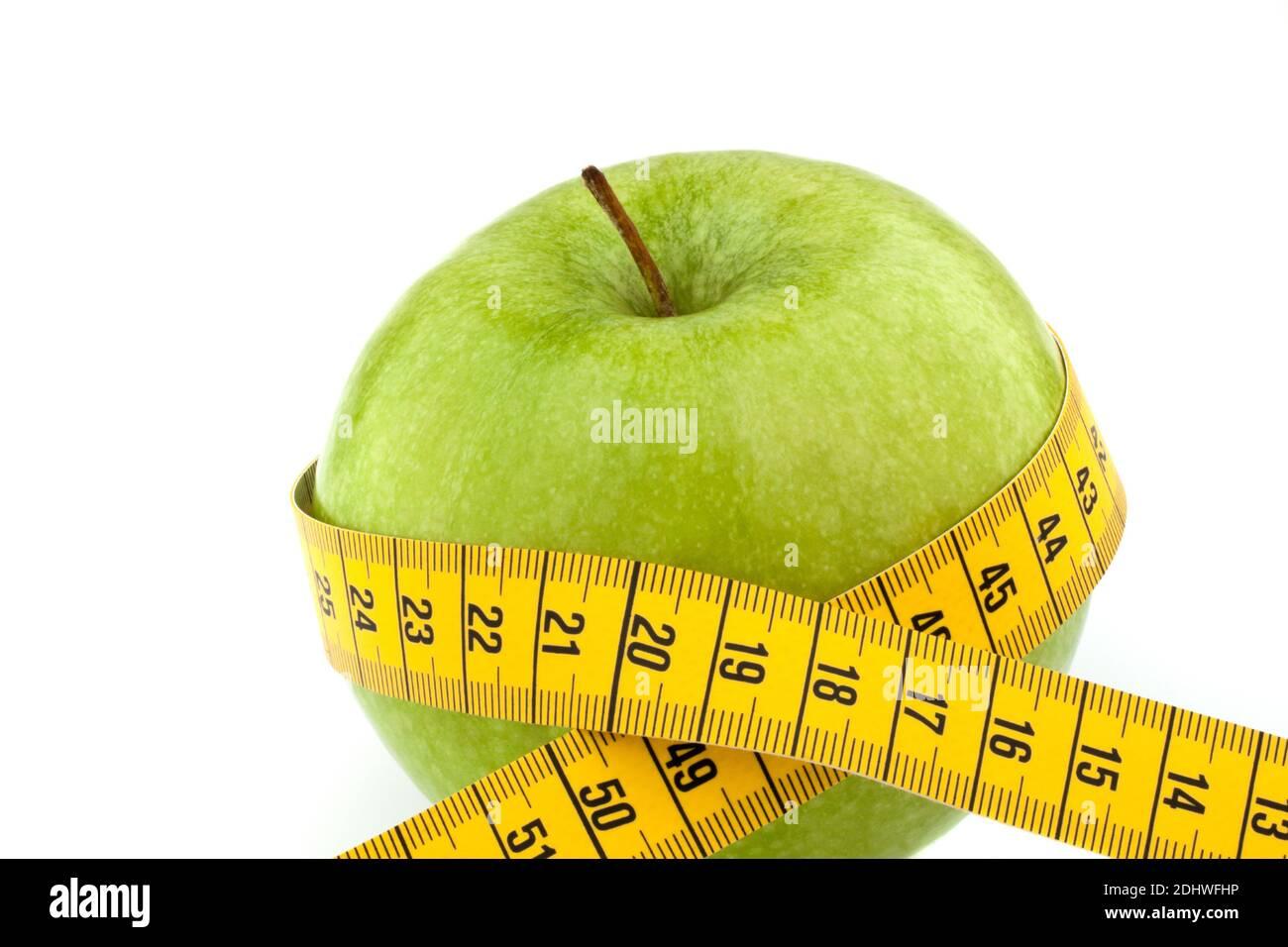 Eingrüner Apfel mit Massband. Symbol für Diät mit Obst. Stock Photo
