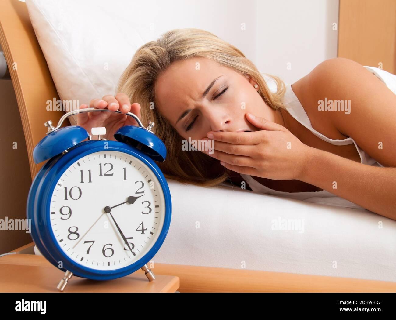 Blonde Frau kann nicht schlafen. Wecker zeigt 2.25 in der Nacht, Stock Photo
