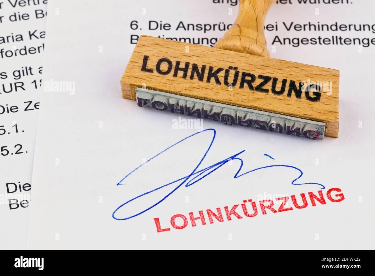 Ein Stempel aus Holz liegt auf einem Dokument. Aufschrift Lohnkürzung Stock Photo