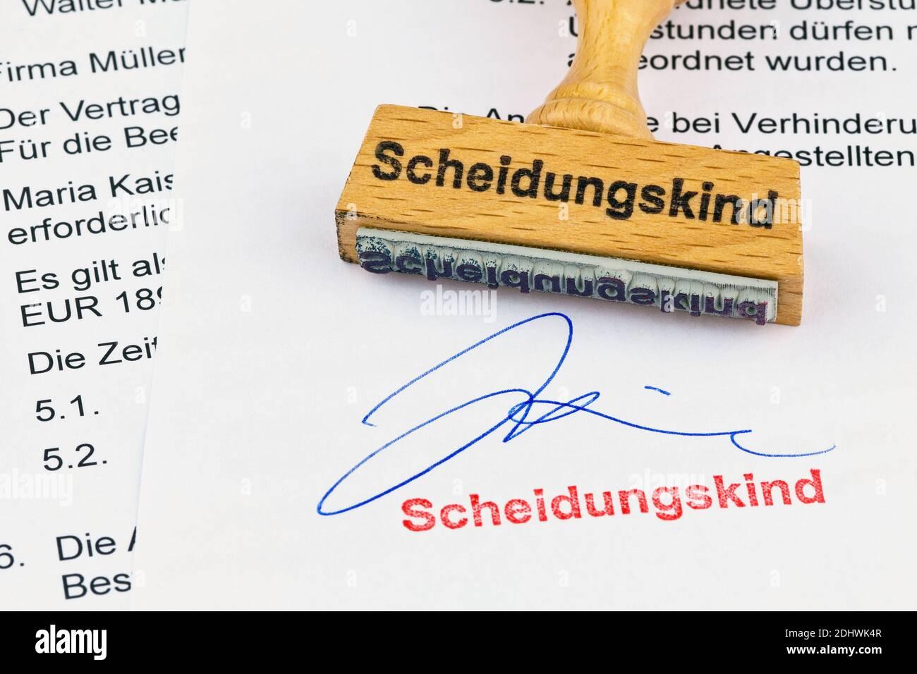 Ein Stempel aus Holz liegt auf einem Dokument. Aufschrift Scheidungskind Stock Photo