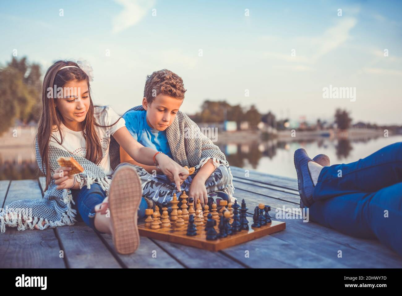 Two young cute little friends, boy and girl having fun while playing chess sitting by the lake in the evening. Kids are playing. Friendship. Selective Stock Photo